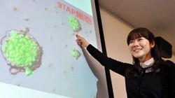 スクリーンのSTAP細胞を指さす理化学研究所発生・再生科学総合研究センターの小保方晴子・研究ユニットリーダー=神戸市中央区で2014年1月28日、川平愛撮影