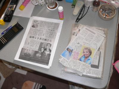 切り取った新聞記事を台紙に張り込んでいく作業風景